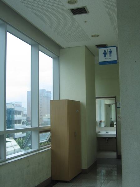 엘리베이터 옆의 화장실로 들어가는 입구. 천장에 새로 설치한 환풍 시설이 보인다. 이 화장실을 이용하기 위해서는   담배연기를 뚫고 지나가야 한다.
