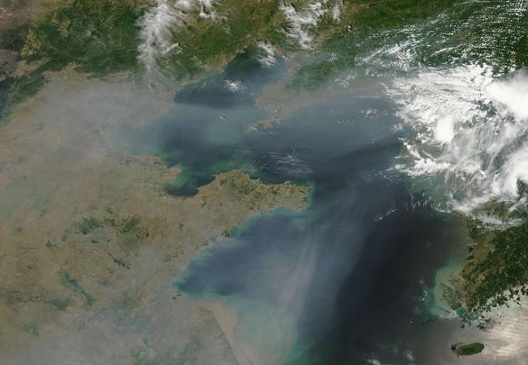 (2009 년 6월 25일 관측된 거대한 대기 오염 물질 Thick haze blown off the Eastern coast of China, over Bo Hai Bay and Yellow Sea. The haze likely results from urban and industrial pollution. Credit : NASA/GSFC, MODIS Rapid Response )