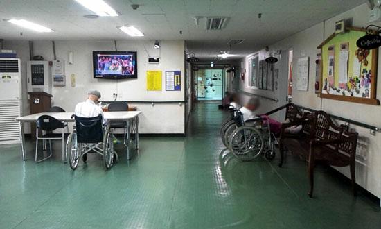 ▲ 경기도 중소도시에 있는 어느 요양원의 로비. 빛이 들어 올 창문 하나 없이 침침한 복도에서 휠체어를 탄 노인 두 명이 벽을 보고 정물처럼 앉아 있었다. ⓒ 손지은