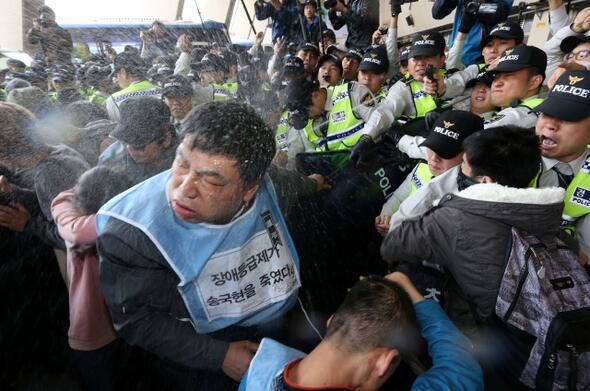 장애인의 날 장애인들의 시위에 최루액을 뿌리는 경찰 (출처)