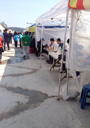 ▲ 팽목항 도로를 따라 봉사단체 및 언론사의 부스가 설치돼 있다. 취재기자들이 천막 아래에서 기사를 작성하고 있다. ⓒ 김선기