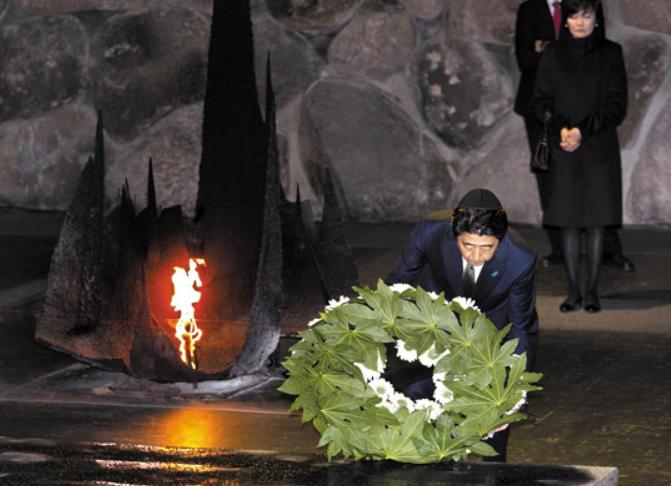 아베 총리가 무릎을 꿇은 채 홀로코스트 기념관에 헌화하는 모습. 뒤에 선 여성은 부인 아키에 여사.
