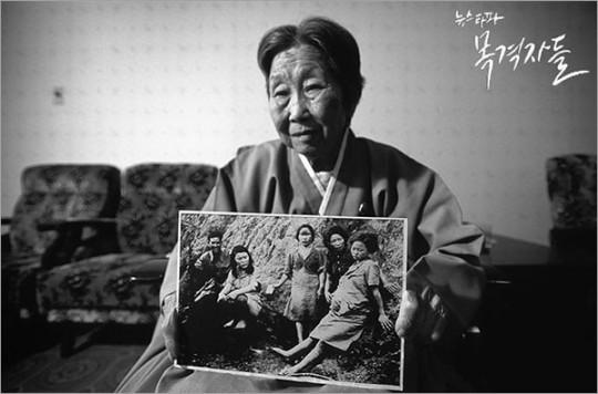 고 박영심 할머니가 자신의 '위안부' 시절 사진을 들어보이고 있는 일본의 사진작가 이토 다카시의 사진