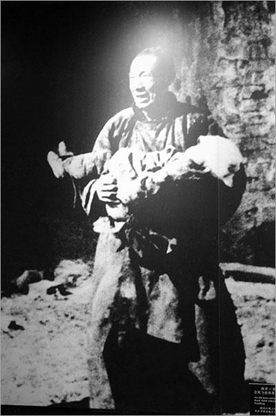 ▲ 죽은 아이를 안고 있는 아버지. 일본군의 학살은 아이, 어른을 가리지 않았다.
