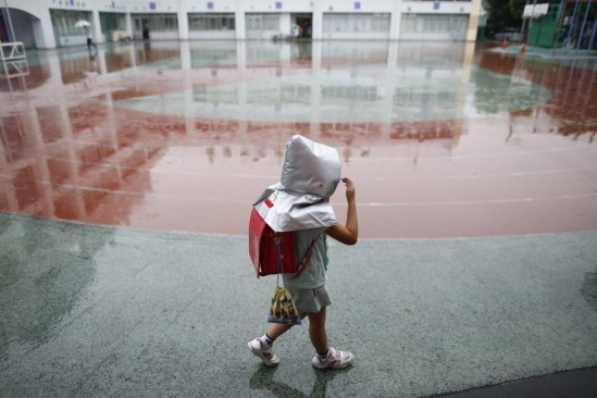 A school girl wearing a padded hood to protect her from falling debris, walks in school field during an earthquake simulation exercise at an elementary school in Tokyo September 1, 2015. The annual exercise is held nationwide on the anniversary of the 1923 Great Kanto Earthquake to practise the response to major natural disasters. REUTERS/Toru Hanai - RTX1QITC