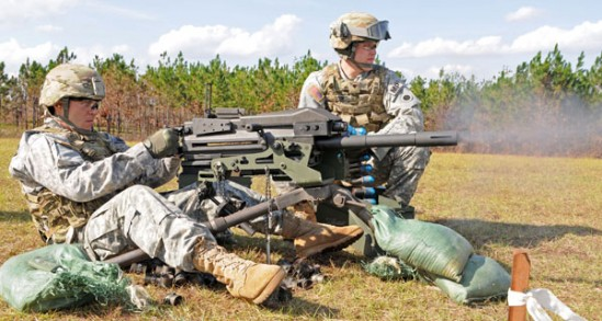 Spc. Patrick L. Noel of Cincinnati, Ohio, continues to fire as his assistant gunner, Spc. Philip J. Gavin of Newark, Ohio, Personal Security Detail Soldiers assigned to Headquarters and Headquarters Company, 37th Infantry Brigade Combat Team, feeds ammunition to their MK19 machine gun during qualification at Camp Shelby Joint Forces Training Center, Miss., Nov. 16, 2011. The 37th IBCT is deploying to Afghanistan in support of Operation Enduring Freedom. (37th IBCT photo by Sgt. Kimberly Lamb) (Released)