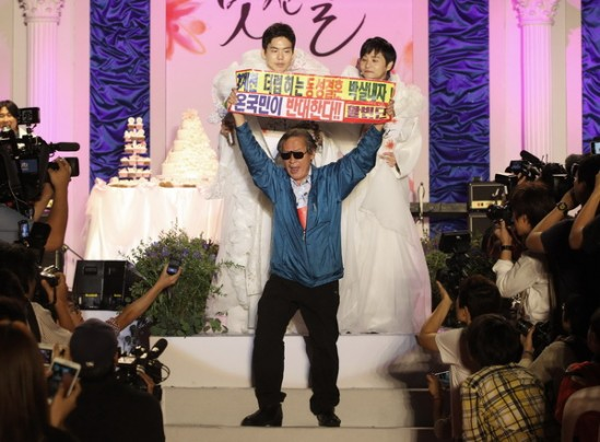"""An anti-gay protester Hong Jung-shik, center, holds up a banner to oppose gay marriage as South Korean movie director Kim Jho Gwangsoo, top right, and his partner Dave Kim stand during their wedding ceremony in Seoul, South Korea, Saturday, Sept. 7, 2013. Director Kim surprised many in May, 2013, by announcing he will symbolically tie the knot with his longtime male partner Sept. 7, in the highest-profile ceremony of its kind ever in South Korea. He and Dave Kim envision a massive public event in Seoul with guests honoring their relations by donating money to build a center for lesbian, gay, bisexual and transgender people. The letters at a banner read """" Opposed same-sex marriage"""". (AP Photo/Ahn Young-joon)"""