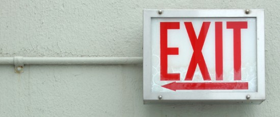 Red exit sign on white-greenish plastered wall
