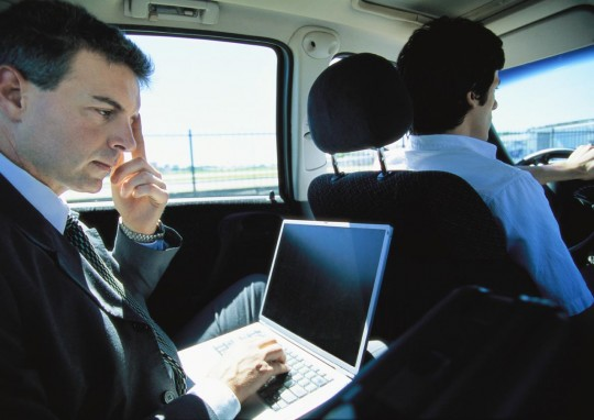 A1ETPE Businessman using laptop in taxi