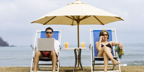 Couple using laptop and phone on beach
