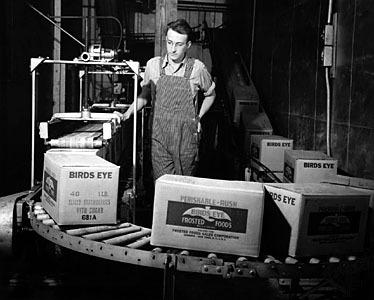 컨베이어 벨트의 냉동식품 상자를 지켜보는 버즈아이사의 노동자