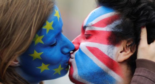 Two activists with the EU flag and Union Jack painted on their faces kiss each other in front of Brandenburg Gate to protest against the British exit from the European Union, in Berlin. REUTERS/Hannibal Hanschke