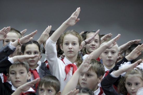 Children, wearing red neckerchiefs, a symbol of the Pioneer Organization, salute while posing for a picture during a ceremony for the inauguration of 18 newly adopted members at a local school in the southern settlement of Kazminskoye in Stavropol region, Russia, November 19, 2015. Early pro-communist youth movements, which appeared in Russia after the 1917 Bolshevik revolution, were reformed into the Pioneer Organization of the Soviet Union. While the organization lost its dominance among students in post-Soviet Russia, some educational institutions and families still carry on this tradition. REUTERS/Eduard Korniyenko - RTS7YMY